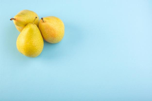 Вид сверху зеленые груши, мясистые, сладкие, сочные и спелые фрукты, изолированные на ледяном синем фоне, фрукты, экзотическое лето