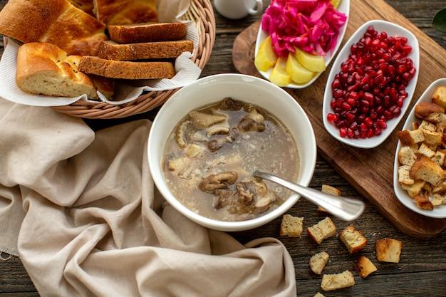 Горячий суп сверху с ломтиками граната и свежими овощами на коричневом деревянном деревенском полу