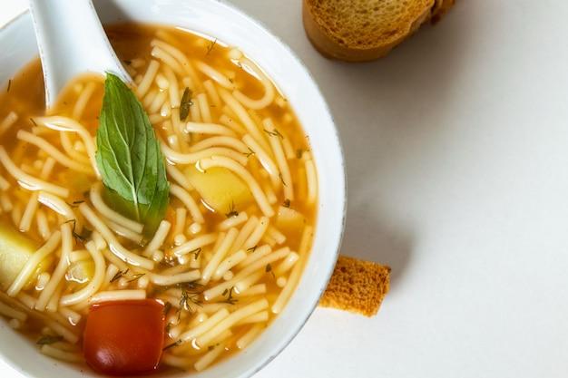 Горячий суп с овощами внутри белых тарелок и ломтиками хлеба на белом, вид сверху