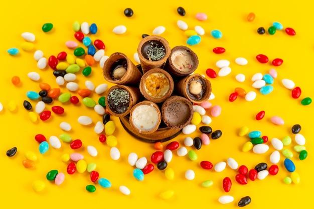 カラフルなキャンディーと一緒に上から見たアイスクリームは、黄色の床色の甘い砂糖の上にすべて広がります