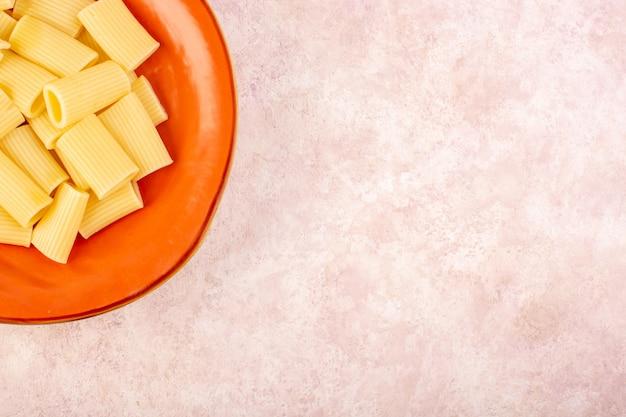 ピンクの机の上の丸いオレンジプレートの内側で美味しくて塩味のイタリアンパスタ