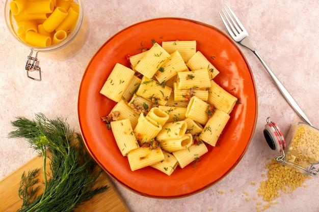 上面図のイタリアンパスタは、ピンクの机の上の緑と生パスタの丸いオレンジプレートの内側においしい塩漬けを調理