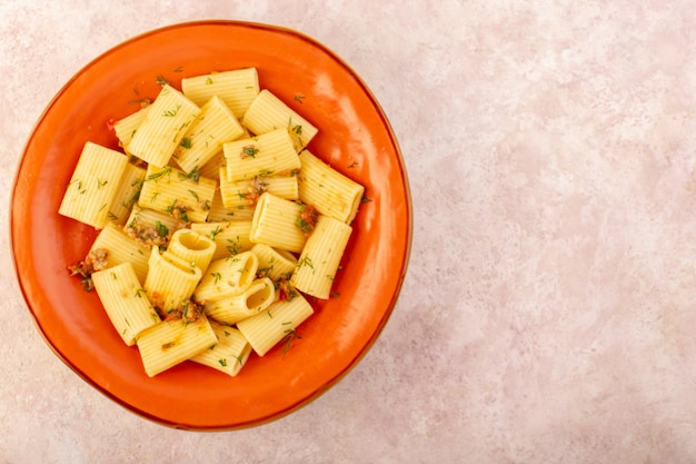 トップビューイタリアのパスタは乾燥した緑とおいしい調理し、ピンクの机の上の丸いオレンジプレートの内側に塩漬け