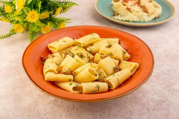 상위 뷰 이탈리아 파스타는 말린 채소로 맛있게 요리하고 분홍색 책상에 꽃과 함께 둥근 주황색 접시 안에 소금에 절인 것입니다.