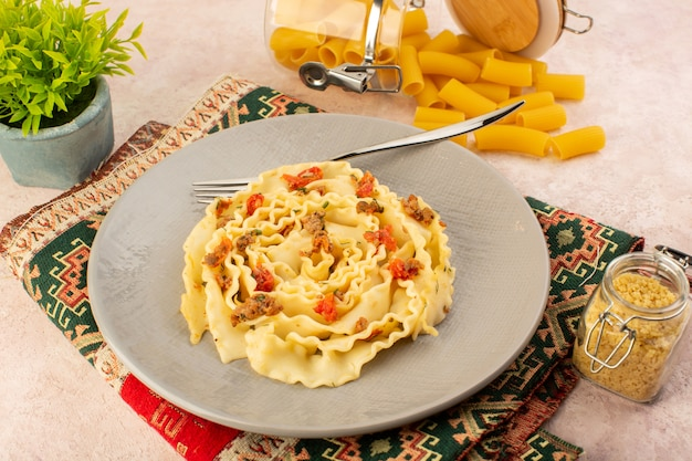Вид сверху итальянской пасты, вкусной еды с приготовленными овощами и маленькими кусочками мяса внутри серой тарелки вместе с сырой пастой на красочном ковре и розовом