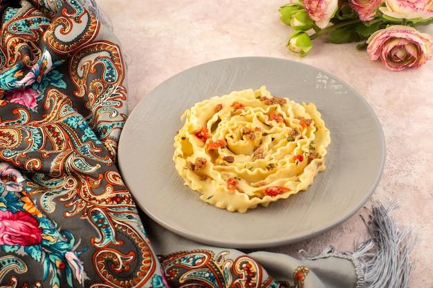 Вид сверху итальянской пасты, вкусной еды с приготовленными овощами и маленькими кусочками мяса внутри серой тарелки на красочном шарфе и розовом