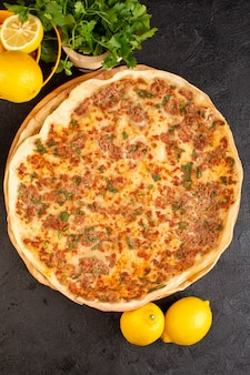 Тесто lahmacun сверху с рубленым мясом и зеленью и лимоном в бумажной коробке вкусная выпечка
