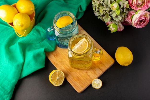 暗い背景のカクテルドリンクフルーツの花と一緒にスライスされたガラスのコップとレモン全体の上面図レモンカクテル新鮮な冷たい飲み物