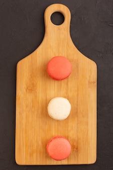 木の板にフランスのマカロンが並ぶトップビュー