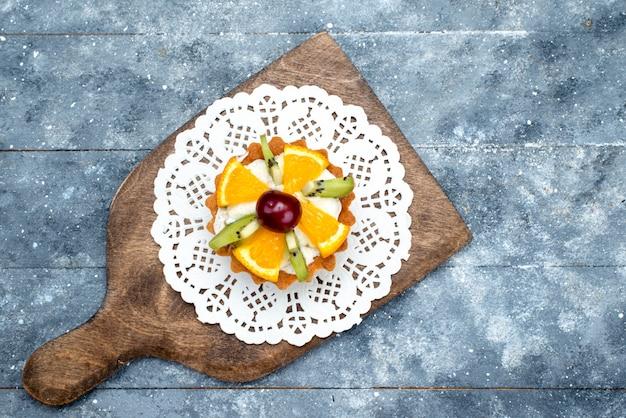 グレーのデスクのフルーツケーキビスケットの上のクリームと新鮮なスライスされたフルーツの小さなおいしいケーキのトップビュー
