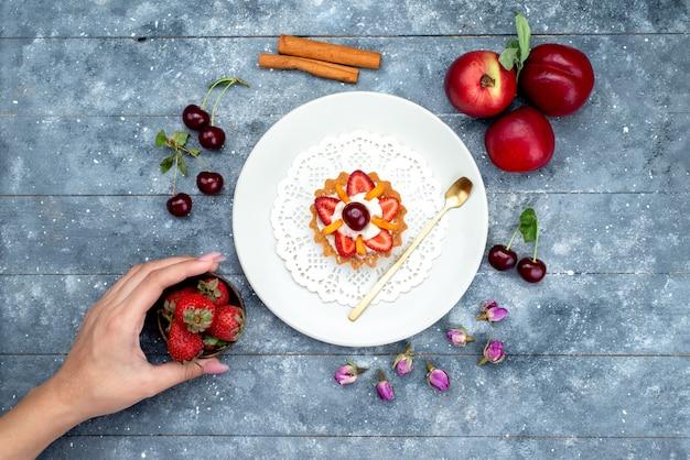 グレーとブルーの背景のフルーツケーキビスケットティーに新鮮なフルーツと一緒に白いプレート内のクリームとフルーツの小さなおいしいケーキのトップビュー