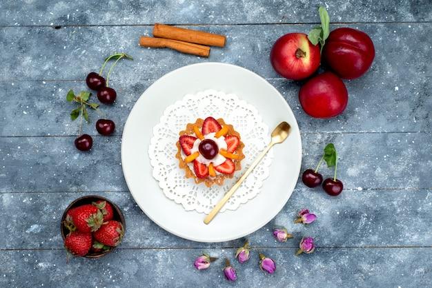グレーとブルーの机の上のフルーツケーキビスケットの新鮮な果物と一緒に、白い皿の中にクリームとフルーツが入った小さなおいしいケーキの平面図