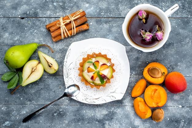 トップビューグレーのデスクケーキビスケットティーにお茶とプレート内のクリームとスライスされたフルーツの小さなおいしいケーキ