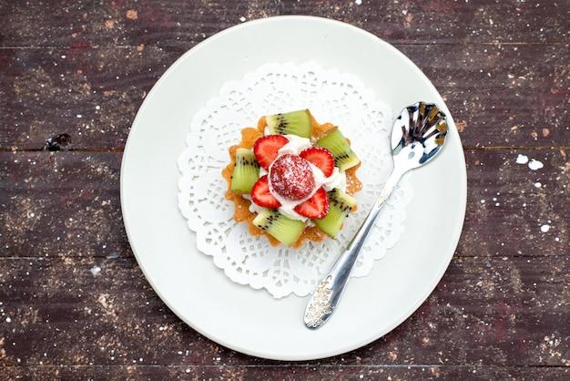 暗い背景のクッキービスケットケーキフルーツに新鮮なイチゴとキウイのプレートの内側にクリームが付いた上面の小さなおいしいケーキ