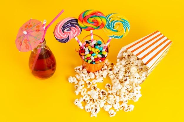 Вид сверху леденцы на палочке и попкорн с коктейлем и разноцветными конфетами на желтом фоне пьют сахарный конфитюр