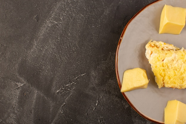 灰色の机の上の鶏の内部とフレッシュチーズの内部プレートとマヨネーズ野菜のサラダ