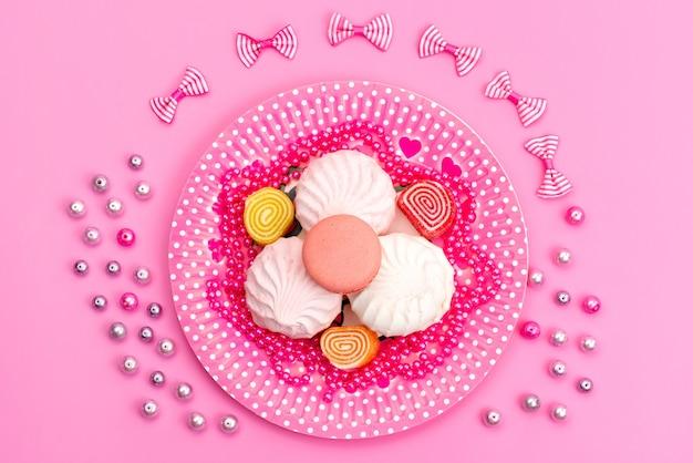 Вид сверху безе и мармелад внутри розового цвета, тарелка вместе с бантами на розовом, торт, сладости, кондитерские изделия