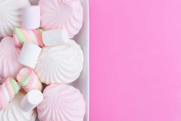 Вид сверху сладкие и вкусные безе и зефир на розовом, сладком бисквите, сладком сахаре