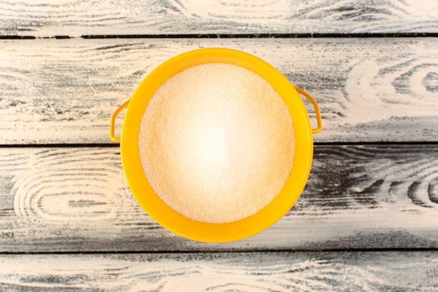 灰色の素朴な木製の机の上の黄色の丸皿の中の多くの塩のトップビュー