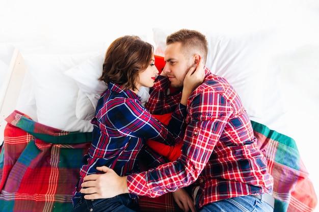 Вид сверху влюбленной пары, которая лежит на кровати и смотрит друг на друга. девушка нежно трогает лицо своего парня