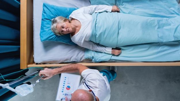 Вид сверху на врача и женщину-пациента с капельницей в постели в больнице.