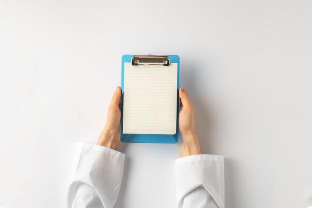 病院のクライアントのためのレシピを書き留めるためにシート紙を持っている医師の手の上面図