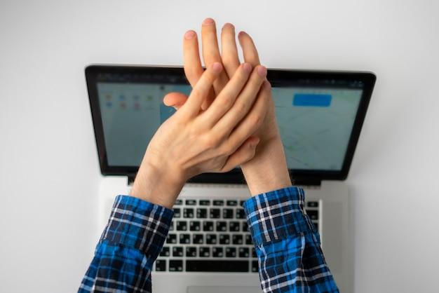 Вид сверху: руки человека закрывают крышку или блокируют веб-камеру ноутбука, опасаясь шпионского взлома камеры