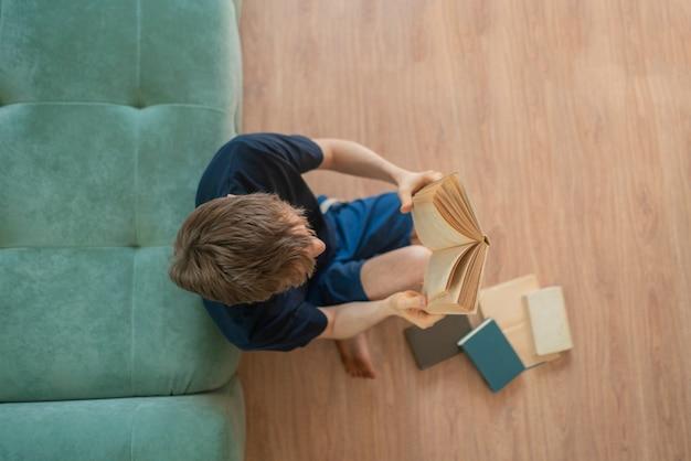 木の床に座って、家で本を読んでいる若い男の上面図