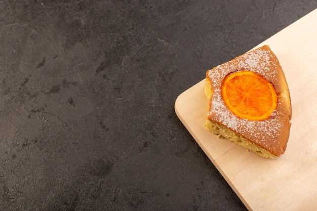 Вид сверху ломтик апельсинового торта сладкий вкусный вкусный на коричневом деревянном столе и сером фоне сладкий сахарный бисквит