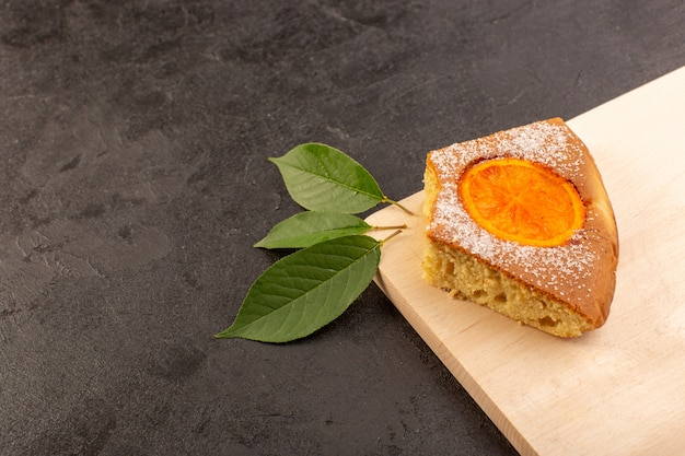 Вид сверху ломтик апельсинового торта сладкий вкусный вкусный на кремовом деревянном столе и сером фоне сладкое сахарное печенье