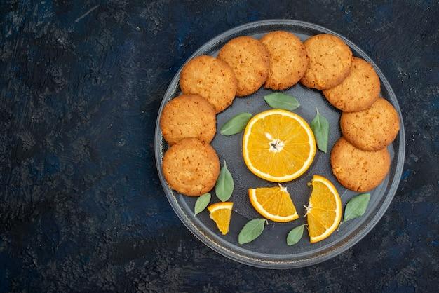 Вид сверху печенье со вкусом апельсина со свежими дольками апельсина внутри тарелки на темном фоне печенье, печенье, сахар, фрукты