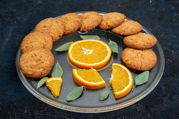 暗い背景のクッキービスケットシュガーのプレート内の新鮮なオレンジスライスとオレンジ色のフレーバークッキーのトップビュー