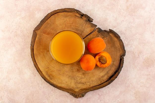 茶色の木製の机の上のオレンジ色のアプリコットとピンクの背景の果物の新鮮な飲み物のビタミンとともに小さなガラスの中の上面オレンジジュース