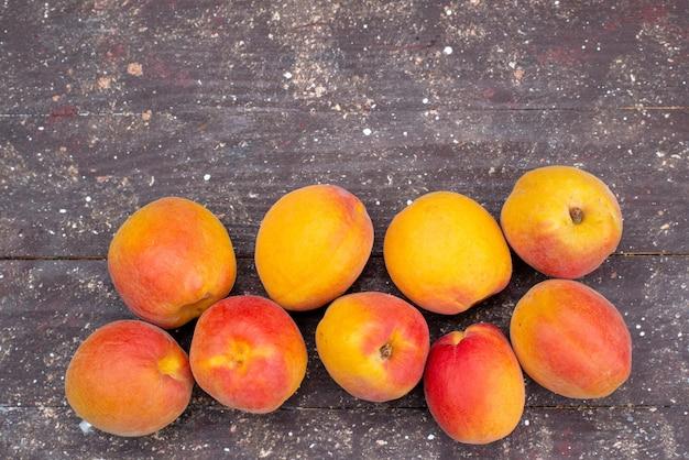 Вид сверху сладкие и сочные персики на деревянном столе фруктовая летняя фото мякоть