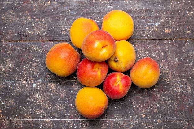 Вид сверху персики, спелые и сочные на деревянном столе, фруктовая летняя мякоть
