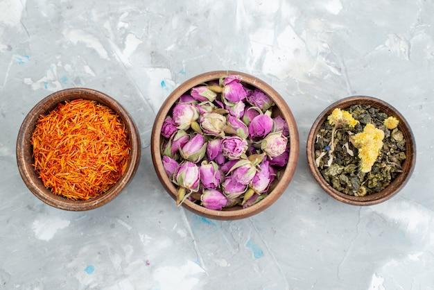 Вид сверху фиолетовые цветы вместе с оранжевым сушеным растением внутри чаш на светлом столе.