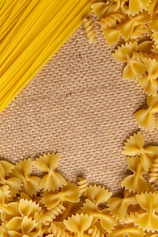 Вид сверху сырые итальянские макароны, маленькие и длинные, разложенные по всей коричневой сумке, паста итальянская еда
