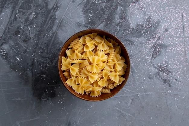 灰色の机の上の茶色のプレートの中に少し形成された生のイタリアンパスタの上面図パスタイタリア料理の食事