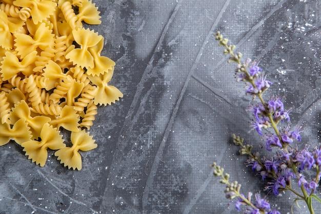 灰色の机の上の紫色の花で少し形成された生のイタリアンパスタの平面図パスタイタリア料理の食事