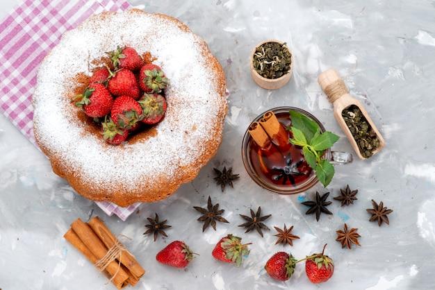 Вид сверху круглый торт с сахарной пудрой, красная клубника, чай с корицей на белом столе, ягодный фруктовый торт