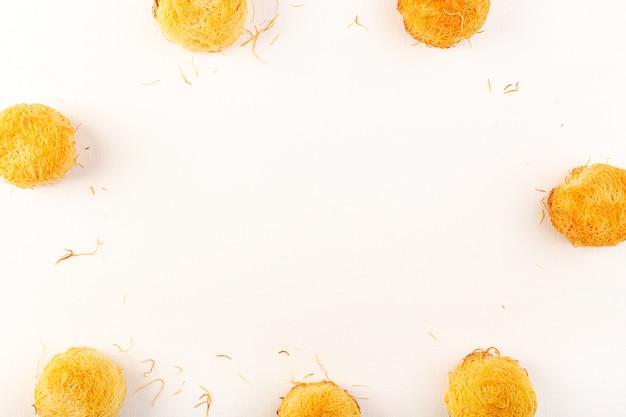 Вид сверху круглые вкусные пирожные сладкие вкусные круглые сдобные пирожные, изолированные выложены на белом фоне сладкие кондитерские изделия из сахара