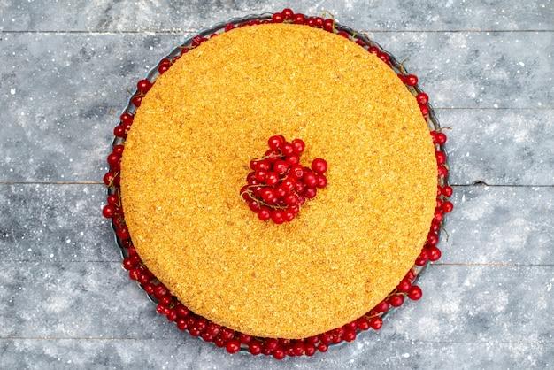 グレーのデスクケーキビスケットシュガー写真のおいしいクランベリーと赤いクランベリーで焼いた蜂蜜ケーキラウンドトップビュー
