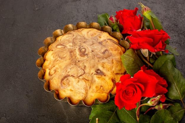 상위 뷰 라운드 달콤한 케이크 맛있고 맛있는 초콜릿 케이크 케이크 팬 안에 빨간 장미와 함께 회색 배경에 설탕 차 비스킷 빵