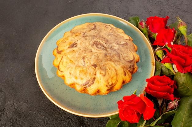 上面図丸い甘いケーキおいしいおいしいチョコレートケーキ灰色の背景に分離された赤いバラと一緒にブループレート内砂糖砂糖ビスケット焼く