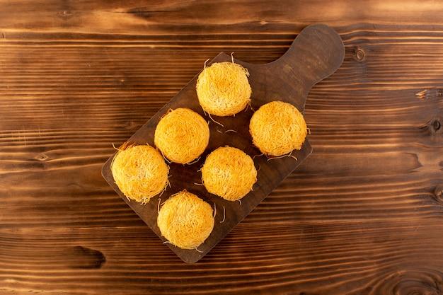 Вид сверху круглые сладкие пирожные вкусные вкусные пирожные изолированные выложены на коричневом деревянном деревенском столе и коричневом фоне сахарного сладкого печенья