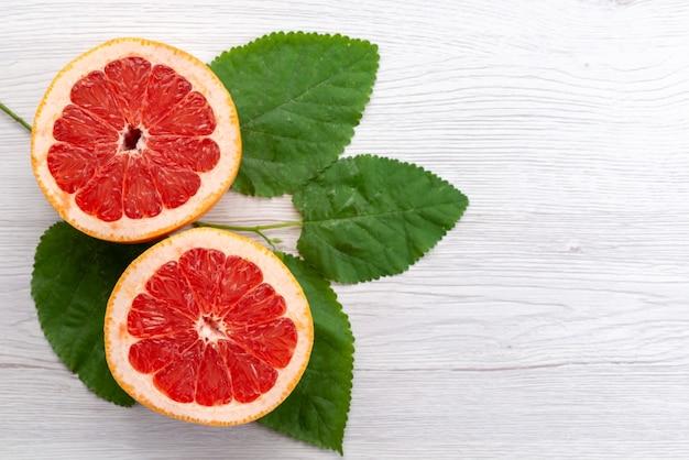 新鮮なグレープフルーツと白い机の上の緑の葉、柑橘系の果物ジュースと共にスライスされた平面図