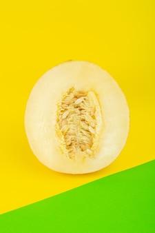 Вид сверху нарезанной свежей дыни, сладкой, мясистой, спелой, изолированной на зелено-желтом