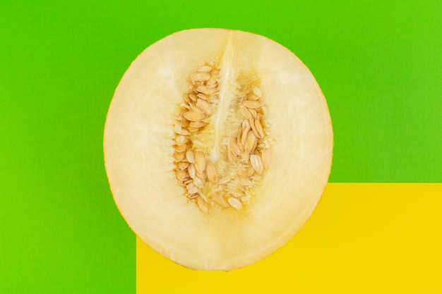 Вид сверху нарезанной свежей дыни, сладкой, мясистой, спелой, изолированной на зеленом