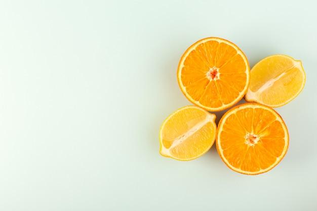 トップビュースライスされたオレンジ色の新鮮な熟したジューシーなまろやかな分離された半分カットピースと白い背景の果物色の柑橘類のスライスされたレモン