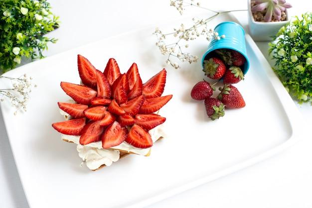 Вид сверху нарезанной красной клубники с сочными сочными ягодами внутри белого стола вместе с цельной клубникой и растениями по всему фруктовому десерту на белом полу.